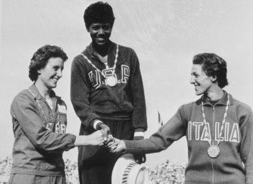 3 AUG 1960:  WILMA RUDOLPH OF THE USA, MIDDLE,  STAND ON THE AWARDS STAND WITH COMPETITORS DOROTHY HYMAN, LEFT, AND G. LEONE AFTER WINNING THE GOLD MEDAL IN THE 200 METER SPRINT AT THE SUMMER OLYMPICS IN ROME, ITALY.   Mandatory Credit: HULTON DEUTSCH/ALL
